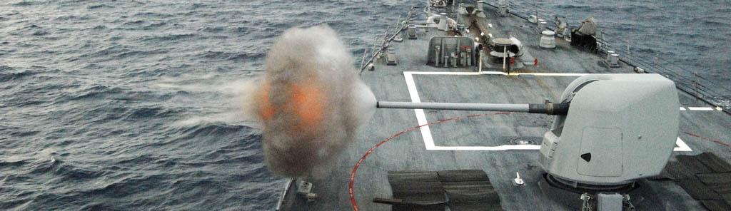 El USS Mahan disparando su cañón MK45. Foto por US Navy, en Flickr (5511908147), con licencia CC by